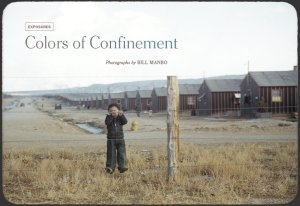 Japanese American boy stands by fence