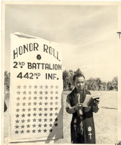 Photo of 442nd Chaplain Hiro Higuchi reading a list of the unit's casualties at a memorial on June 26, 1944.