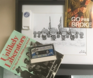 Image of 442nd memorabilia, including a 'Go For Broke' CD, framed 'Journey of Heroes' comic panel, copy of 'Unlikely Liberators' with one of the oral history interview tapes used in the book, and a souvenir 'Go For Broke' pill cutter case