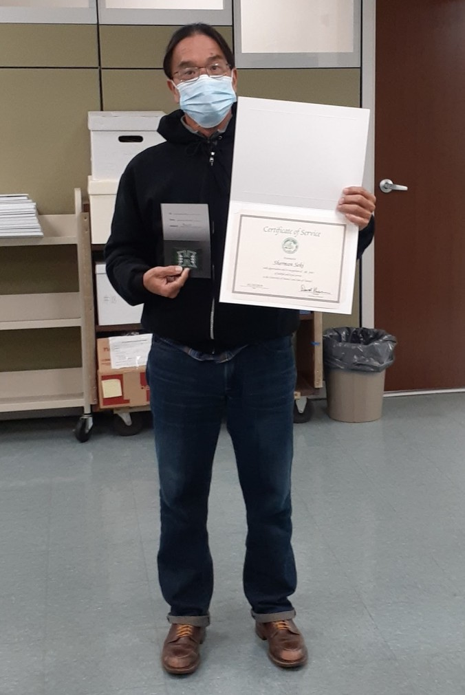 Photo of University Archives & Manuscript Collections Department Library Assistant Sherman Seki posing with his 30 year service award, 2020