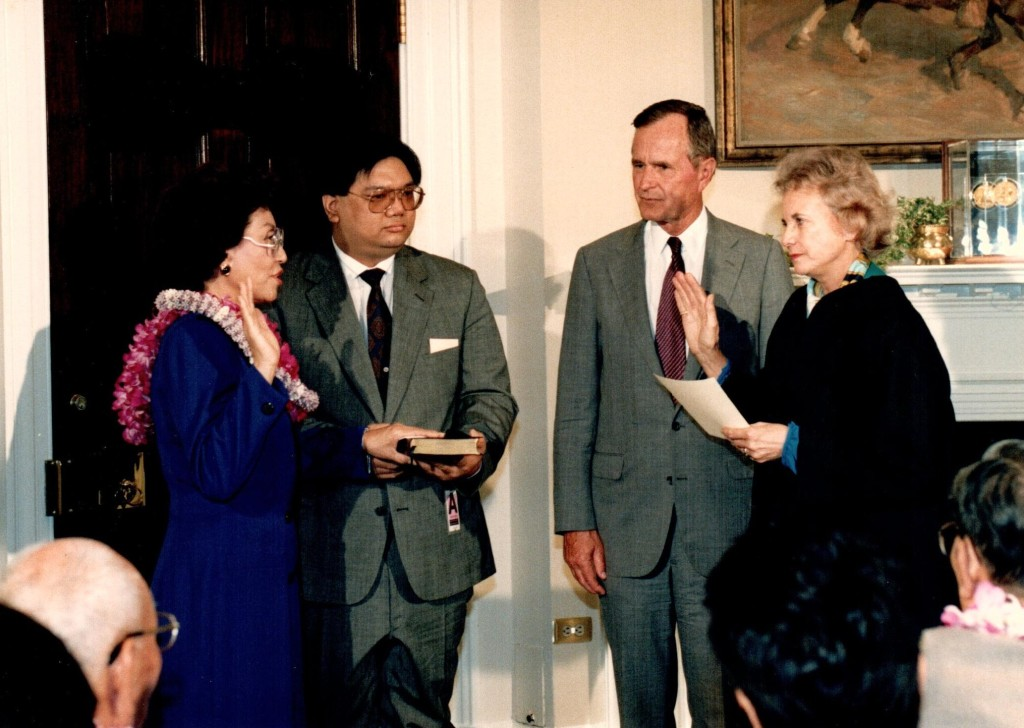 Pat Saiki being sworn in as administrator of the Small Business Administration by Justice Sandra Day OʻConnor. Saikiʻs son Stanley Jr. holds the bible, and President George H. W. Bush looks on. April 10, 1991. Photo: Marty La Vor.  Patricia F. Saiki Papers, Hawaiʻi Congressional Papers Collection, University Archives & Manuscripts Department, University of Hawaiʻi at Mānoa Library.