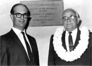 Two men standing in front of the new commemorative plaque at the Snyder Hall renaming dedication ceremony in March 1968. The man on the right (with lei) is Laurence Snyder.